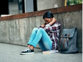 female-college-student-sitting-on-ground-with-knees-pulled-towards-chest-and-hands-near-head-while-dealing-with-symptoms-of-substance-abuse