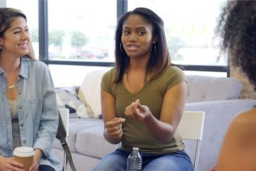 young-woman-sitting-on-couch-and-speaking-during-group-therapy-session