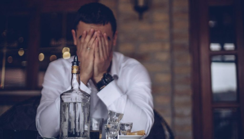 young-man-covering-face-with-hands-in-bar-with-bottle-of-alcohol-on-counter