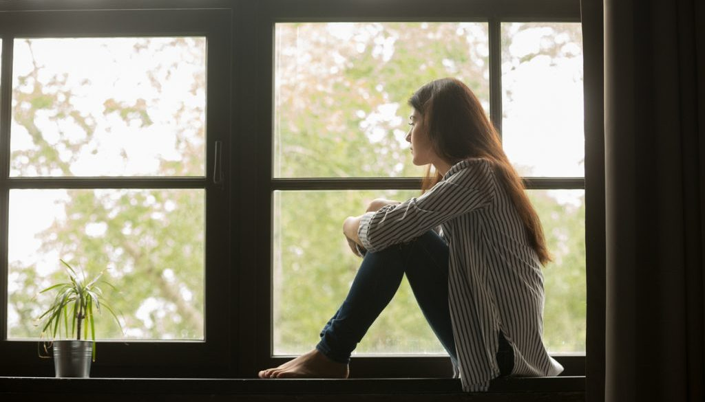 woman-sitting-with-knees-pulled-up-on-windowsill-while-looking-outside-at-trees