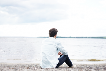 man-in-white-shirt-sitting-on-beach-and-looking-out-to-sea