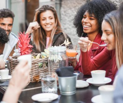 group of young adults enjoying meal together at outdoor table