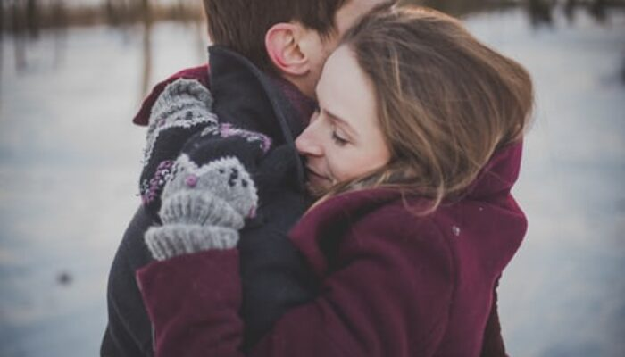 man in black coat hugging woman in purple coat outside in snow