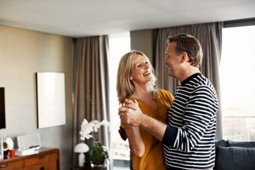 man-and-woman-slow-dancing-and smiling-in-living-room