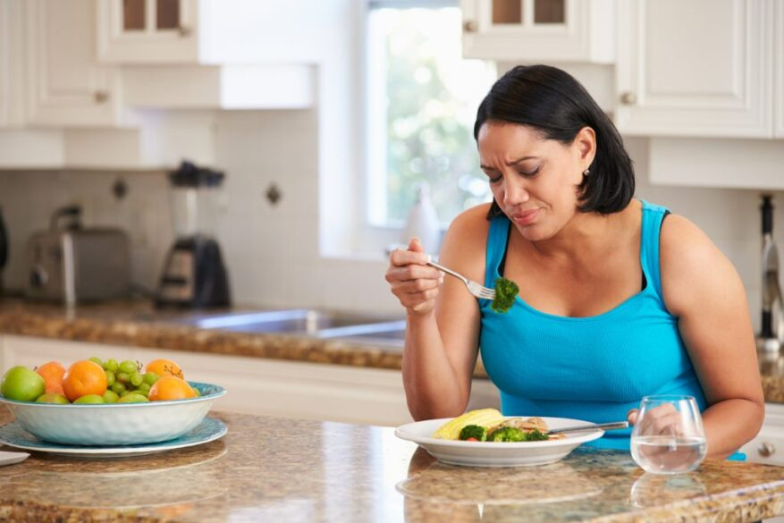 woman sitting at kitchen island with plate of food, looking dejectedly at broccoli on fork