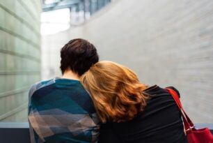 man-and-woman-sitting-together-outside-near-beige-brick-walls